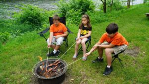 kids camping roasting hot dogs